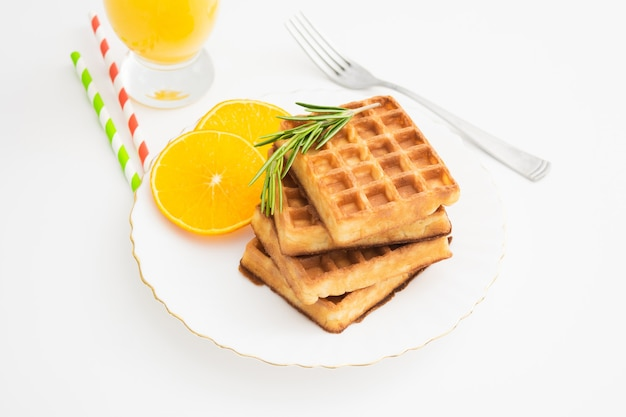 로즈마리와 오렌지 슬라이스로 벨기에 와플을 곁들인 아침 식사. 근접 촬영보기