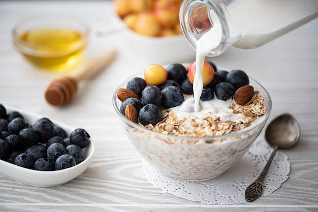ブルーベリーと黄色のサクランボのオートミールが牛乳を注いだ朝食