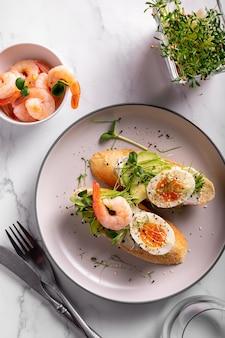 Завтрак с брускеттой с креветками, яйцами и микрозеленью в тарелке, крупным планом