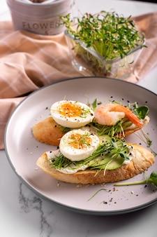 プレートにエビ、卵、マイクログリーンを添えたブルスケッタの朝食、クローズアップ