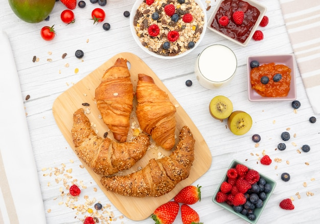 Завтрак с масляным круассаном и кукурузными хлопьями, смешанными с целыми дождями и группой фруктов