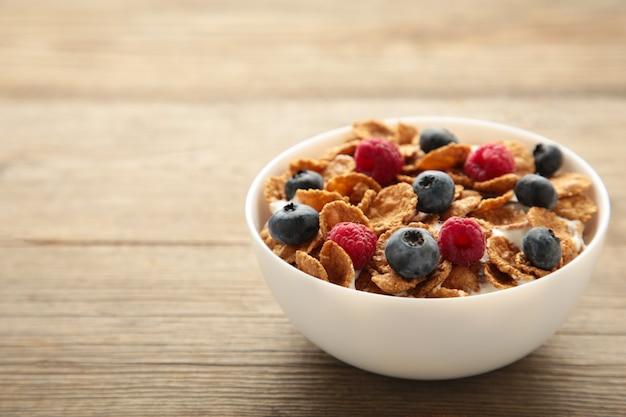 회색 배경에 시리얼과 베리로 구성된 아침 식사. 평면도.