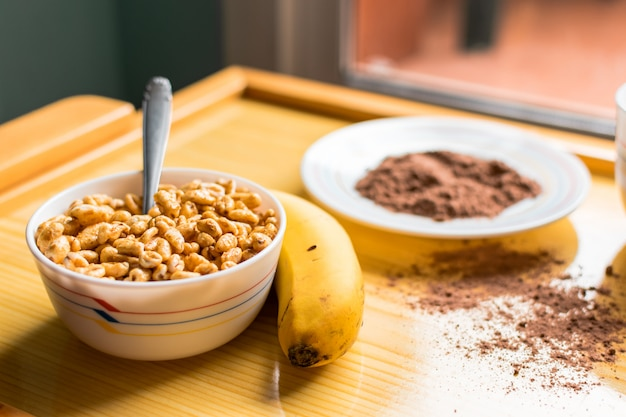 Breakfast with cereals in a bowl with milk, cocoa and banana