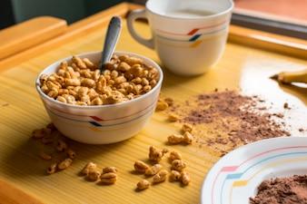 牛乳、ココア、バナナをボウルにシリアルで朝食します。