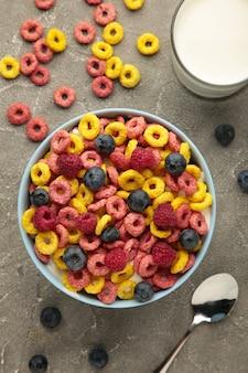회색 배경에 시리얼, 우유, 베리로 구성된 아침 식사. 평면도. 세로 사진