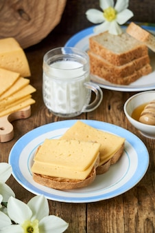 Breakfast with cheese sandwich, milk and honey on a wooden table