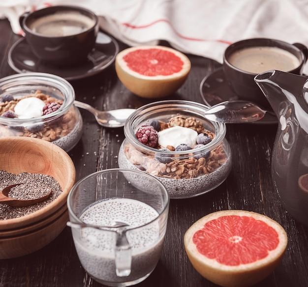 木製のテーブルでチア、ヨーグルト、グラノーラと朝食