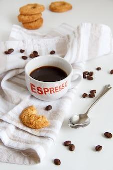 コーヒーとクッキーと朝食は白いテーブルにクローズアップ