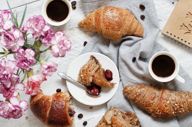 コーヒーとクロワッサンといちごジャムの朝食のクローズアップ