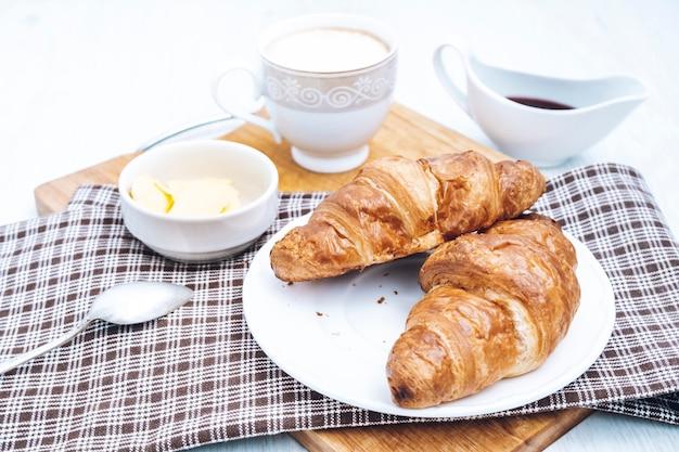 コーヒーとクロワッサンのトップビューで朝食します。ホテルでのコンチネンタルブレックファースト。ベッドでの朝食。