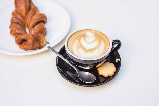 Breakfast with coffee and a bun on a white table in a restaurant.