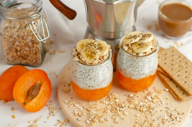 Breakfast with coffee, crackers, oat flakes, chia seed pudding with banana and apricot on wooden board