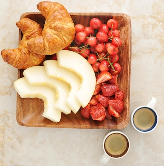 Breakfast with coffee, croissants and fruit - melon, strawberries, cherries in a wooden bowl.