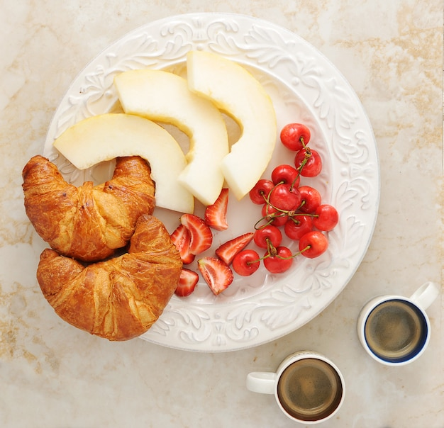 Breakfast with coffee, croissants and fruit - melon, strawberries, cherries