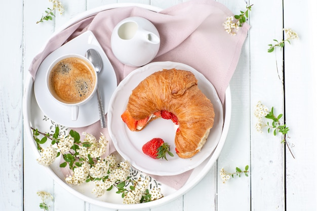 Breakfast with coffee and croissants. light key