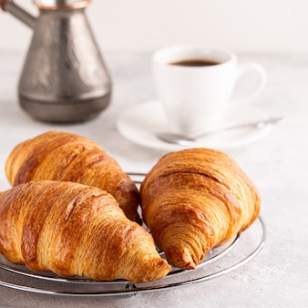 Breakfast with coffee and croissants, selective focus