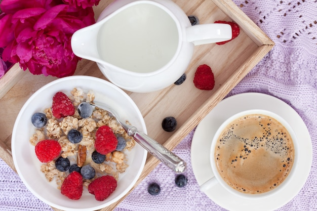 Breakfast with coffee, granola, berries and milk