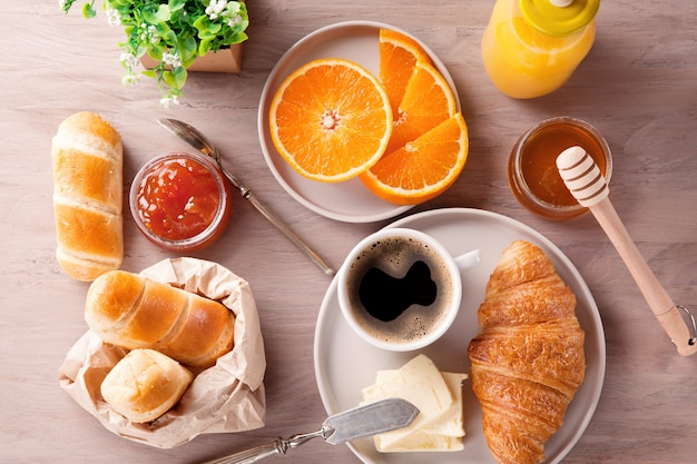 Breakfast with coffee, orange juice and croissant. top view