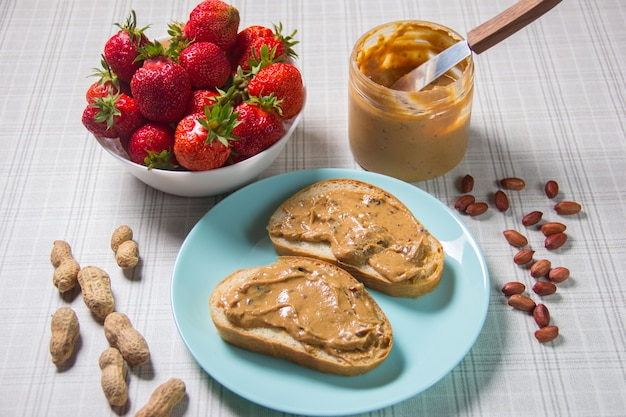 Breakfast with coffee and sandwiches with peanut paste and strawberries
