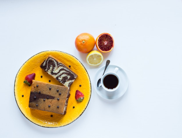 Breakfast with coffee and tea with different pastries and fruits on a white wooden table