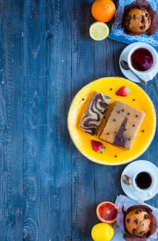 Breakfast with coffee and tea with different pastries and fruits on a wooden table