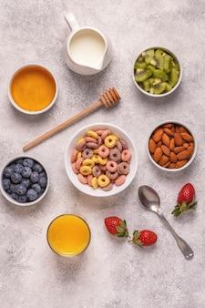 Завтрак с разноцветными зерновыми хлопьями, фруктами, молоком и апельсиновым соком