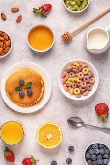 カラフルなシリアルリング、パンケーキ、フルーツ、牛乳、ジュースを含む朝食