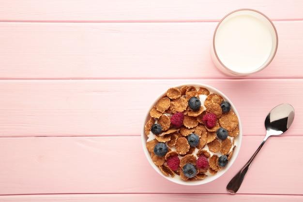 분홍색 배경에 콘플레이크, 우유, 베리로 구성된 아침 식사. 세로 사진