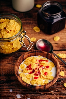 Breakfast with corn flakes, milk and berry syrup