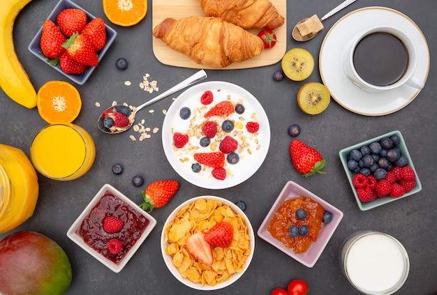 Завтрак с кукурузными хлопьями, смешанными с цельными зернами и группой фруктов