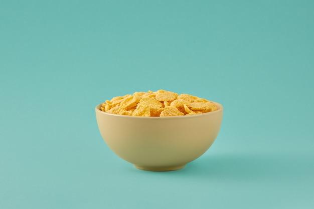 밝은 파란색 배경에 고립 된 그릇에 콘플레이크와 함께 아침 식사