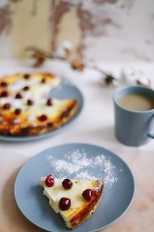 Завтрак с творожной запеканкой с ягодами и чашкой кофе на столе, вид