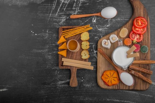 クラッカーと黒の背景に分離された野菜の朝食