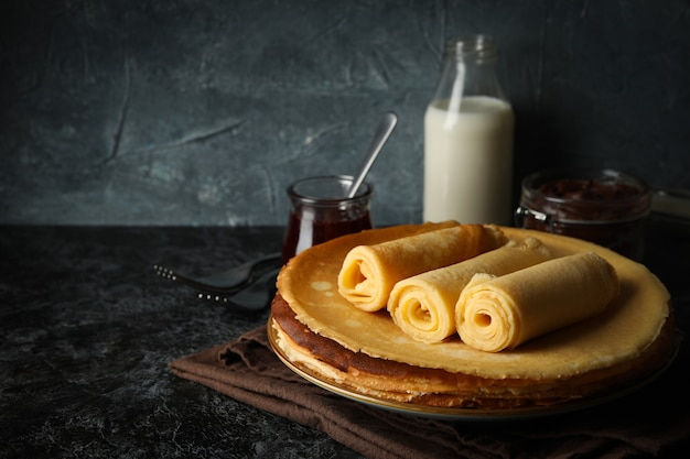 Breakfast with crepes rolls on black smokey table