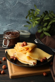 Breakfast with crepes with chocolate paste and nuts on wooden table