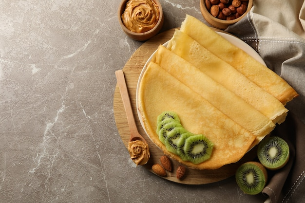 Breakfast with crepes with kiwi, peanut butter and nuts on gray surface