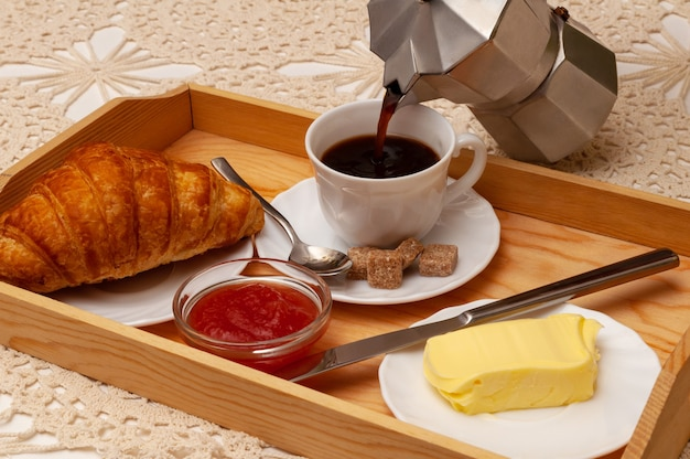 Breakfast with croissant, coffee, jam and butter served on the wooden tray