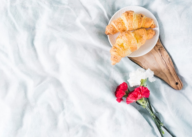 Breakfast with croissant and flowers