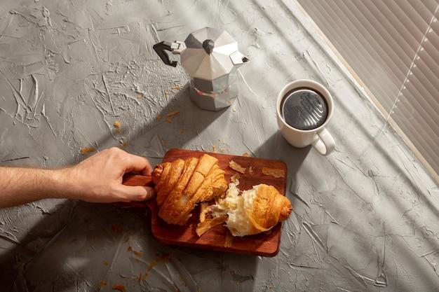 まな板にクロワッサンとブラックコーヒーを添えた朝食。朝の食事と朝食のコンセプト。