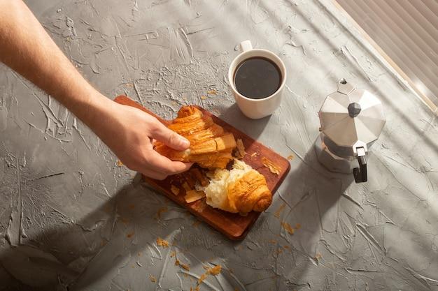 커팅 보드와 블랙 커피에 크루아상으로 아침 식사. 아침 식사와 아침 식사 개념.