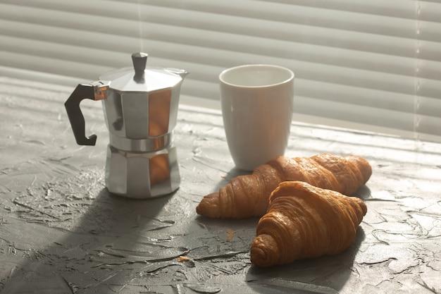 まな板にクロワッサンとブラックコーヒーを添えた朝食。朝の食事と朝食。