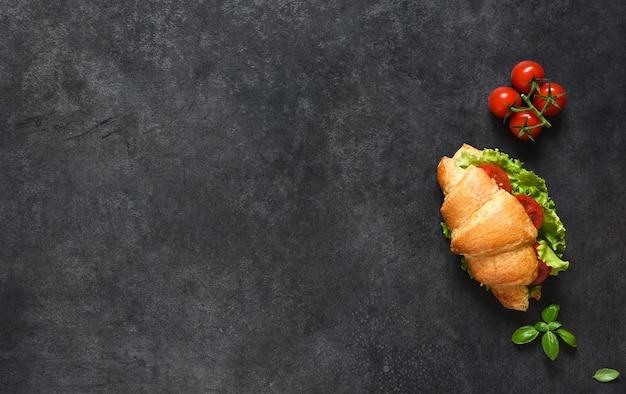 サラダの葉、ハム、チェリートマトのクロワッサンサンドイッチ、黒地にソースを添えた朝食。上からの眺め。