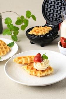 クロワッサンワッフルまたはクロッフル、イチゴとクリームチーズを上に乗せた自家製の焼きたての朝食。ミントリーフを飾る。
