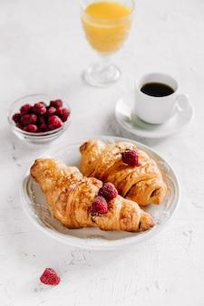 Завтрак с круассанами, чашкой кофе, малиной и апельсиновым соком, вид сверху