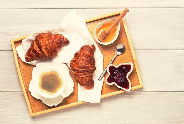 クロワッサンと一杯のコーヒーを入れた朝食、ベッドで、朝、人なし、調子を整える、。高品質の写真