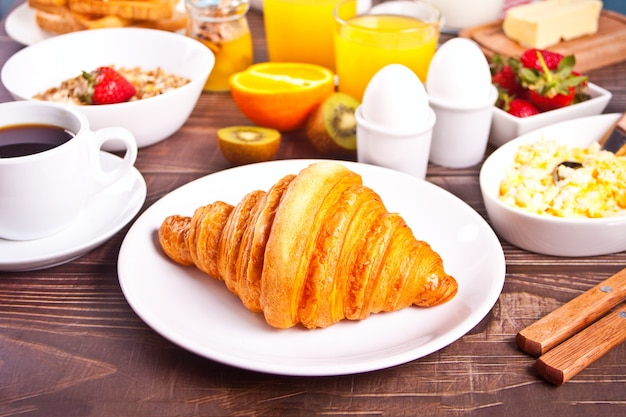 Breakfast with croissants, cup of black coffee, scrambled and boiled eggs, orange juice