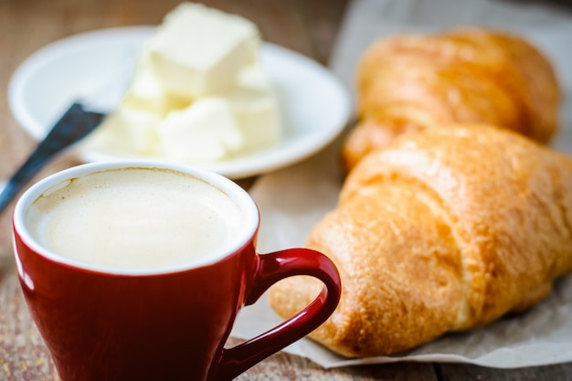 Breakfast with cup of coffee and croissants with butter