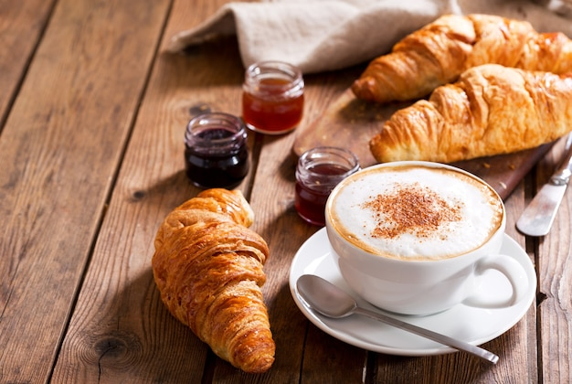 Завтрак с чашкой капучино с круассанами на деревянном столе