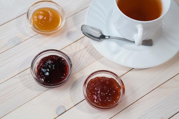 お茶とイチゴ、スグリとアプリコットゼリーまたはジャムと素朴な木製の白い背景の上の朝食、クローズアップ