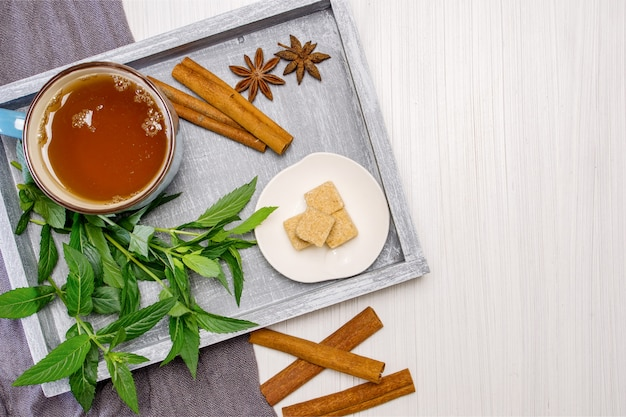 Breakfast with cup of tea on a tray with starlets of anise and chopsticks of cinnamon